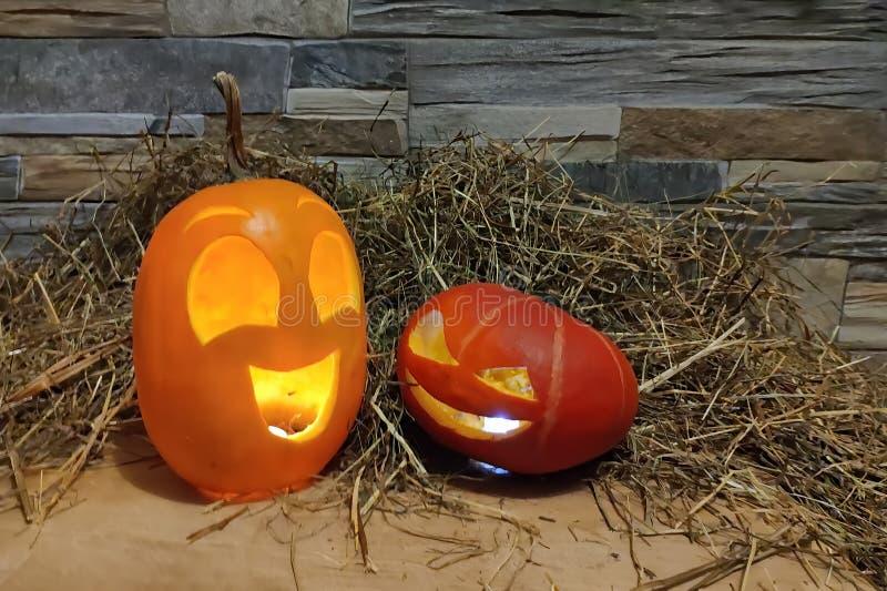 Due lanterne della presa o di Halloween gialle e rosse su un fondo del muro di mattoni e del fieno fotografie stock libere da diritti