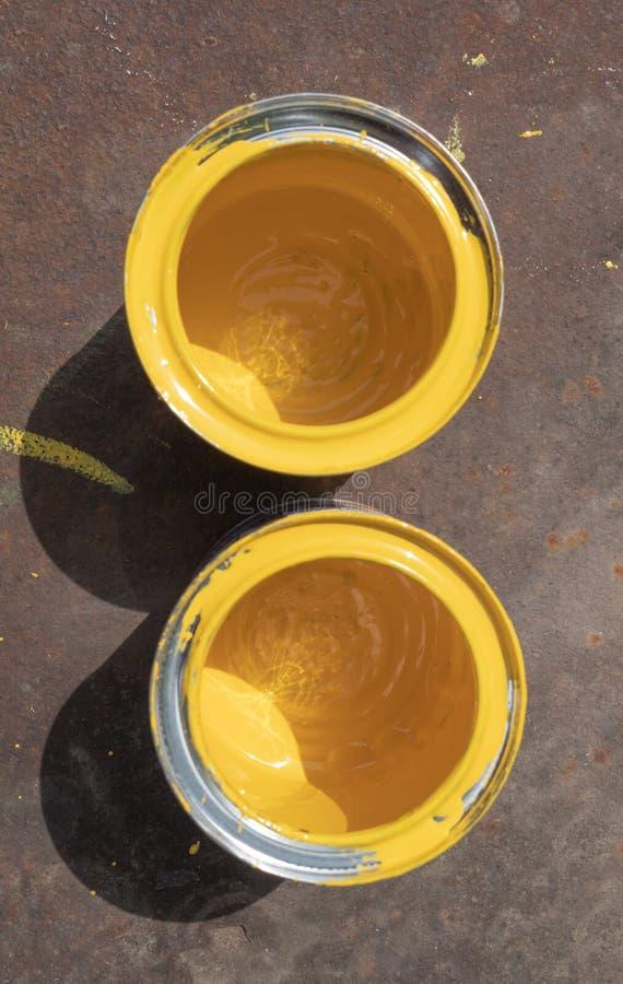 Due latte gialle vuote della pittura con le macchie stanno su uno strato arrugginito del ferro acceso da luce solare fotografia stock libera da diritti