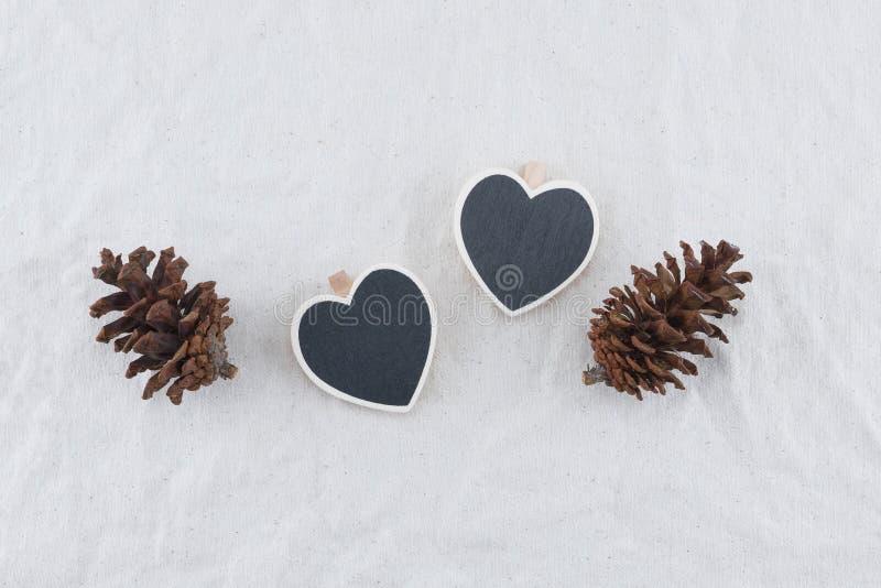 Due lavagne minuscole di forma del cuore con i pinecones fotografie stock