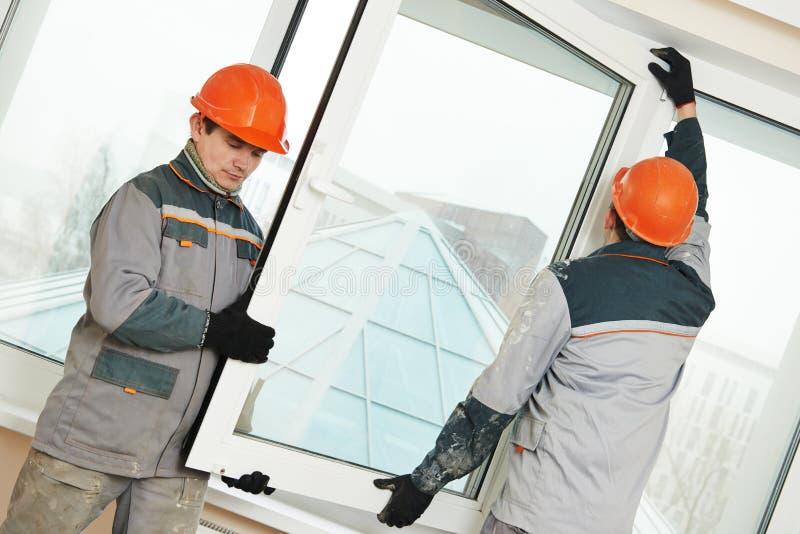Due lavoratori che installano finestra fotografia stock