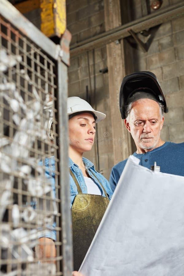 Due lavoratori che progettano produzione della costruzione del metallo fotografia stock