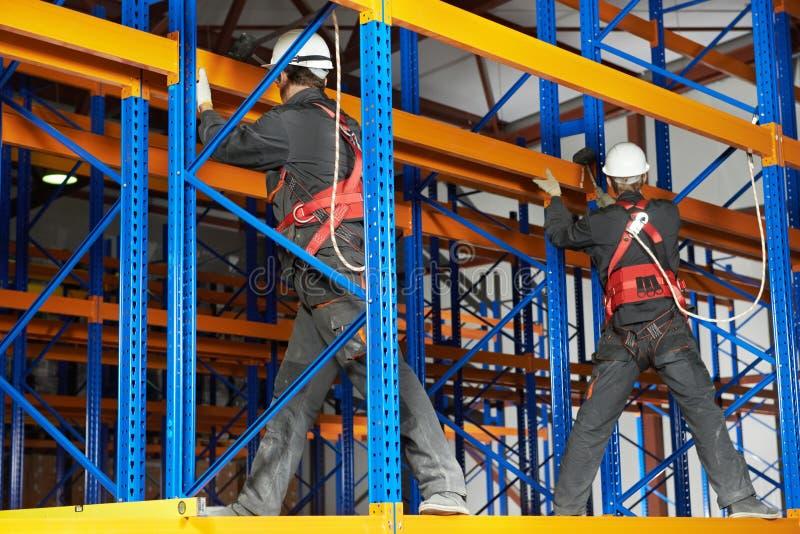 Due lavoratori del magazzino che installano disposizione dello scaffale immagini stock libere da diritti