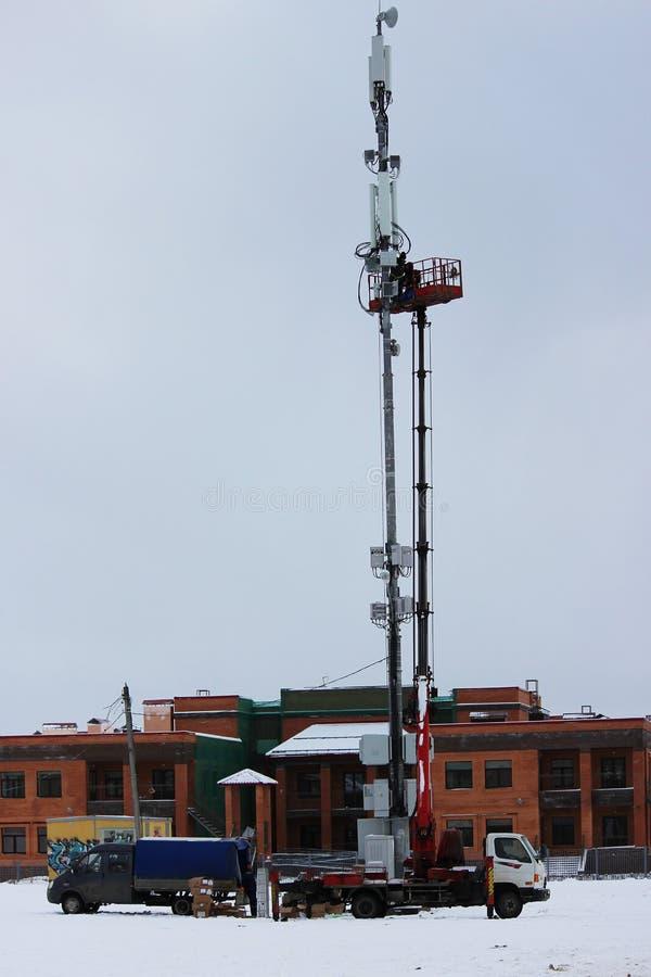 Due lavoratori montano l'attrezzatura per le telecomunicazioni sulla torre per mezzo dell'ascensore nell'inverno fotografia stock libera da diritti