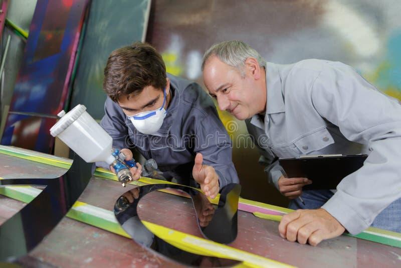 Due lavoratori professionisti dei pittori della fabbrica che dipingono metallo immagini stock libere da diritti