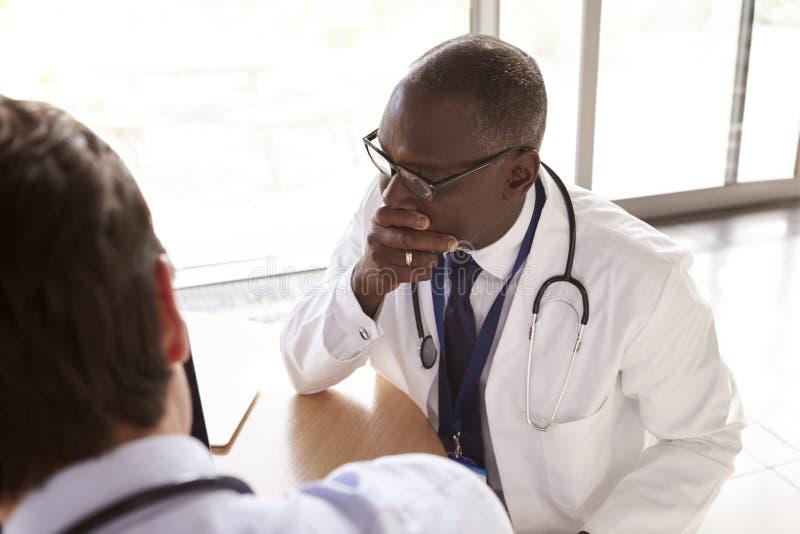 Due lavoratori senior di sanità nella consultazione, sopra la spalla fotografia stock libera da diritti