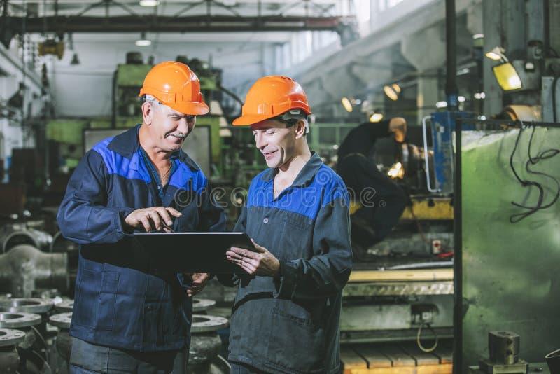 Due lavoratori in un impianto industriale con una compressa a disposizione, workin immagini stock
