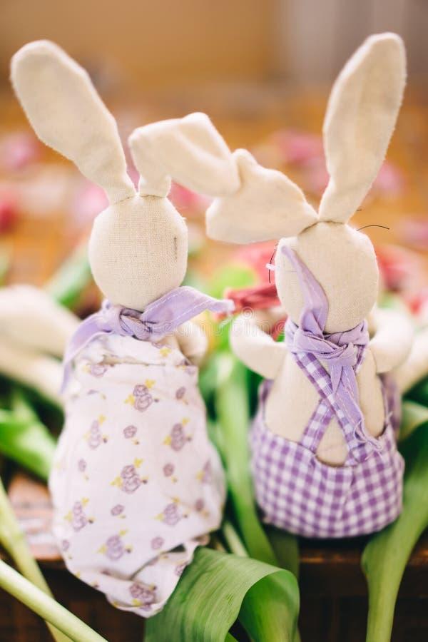 Due lepri del giocattolo stanno sedendo sui fiori Vista posteriore Lavoro manuale Concetto di Pasqua fotografie stock libere da diritti