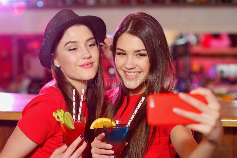 Due lesbiche delle ragazze ad un partito nel club prendono un selfie immagini stock
