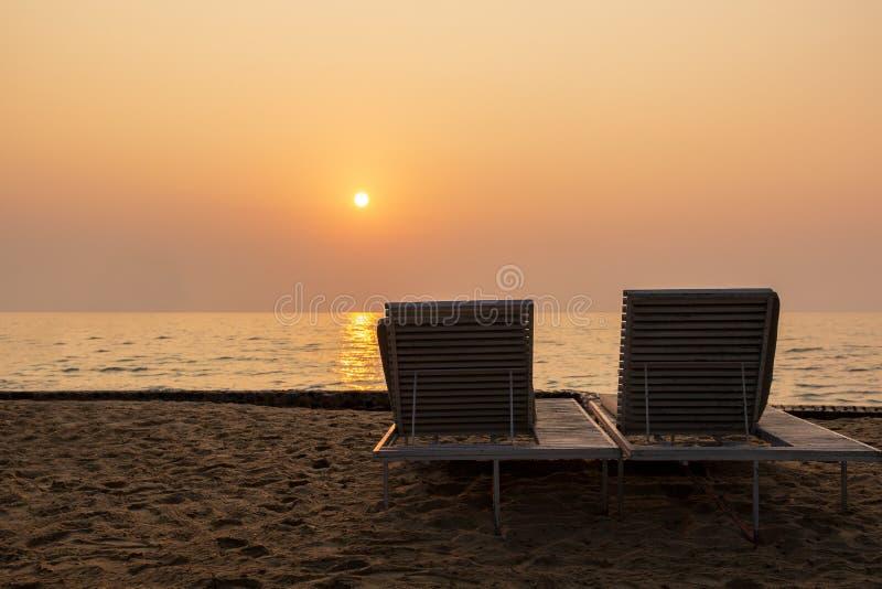 Due lettini vuoti sulla spiaggia contro il bello tramonto sopra l'oceano fotografia stock