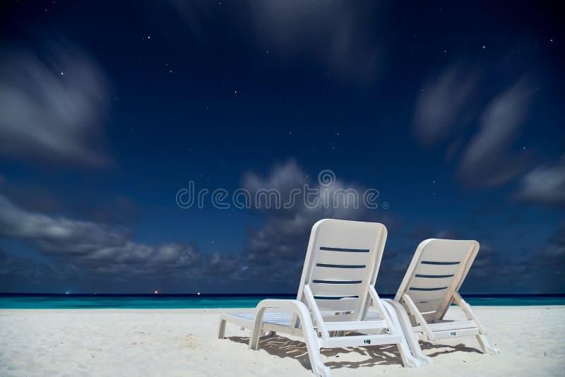 Due lettini vuoti sulla spiaggia dell'oceano sotto cielo notturno con le stelle fotografie stock libere da diritti
