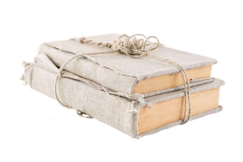 Due libri d'annata in un vecchio panno coprono, riavvolto di filo con un nodo, su un fondo isolato bianco Struttura orizzontale fotografia stock