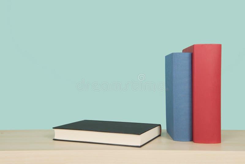 Due libri rosso e condizione del blu e un libro nero che si riposa su uno scaffale di legno su un fondo blu immagine stock libera da diritti