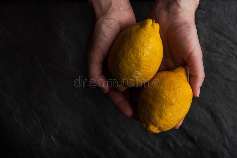 Due limoni nelle mani sulla tavola di pietra nera fotografie stock