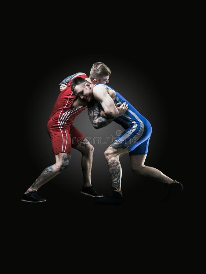 Due lottatori di stile libero in uniforme che lottano sul fondo nero immagini stock libere da diritti