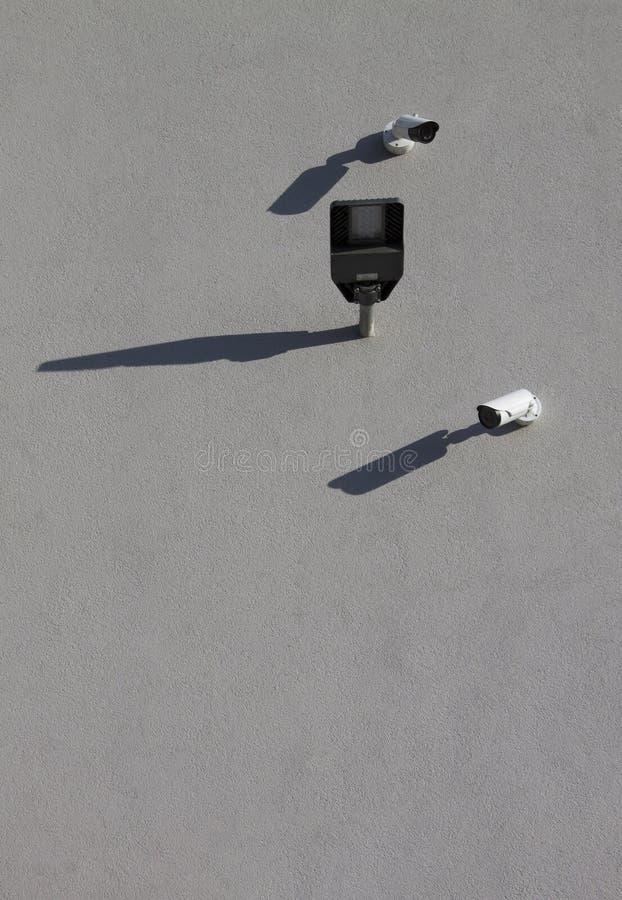 Due macchine fotografiche e lampade di via securty bianche sul parcheggio del monitoraggio della parete|ombra fotografia stock