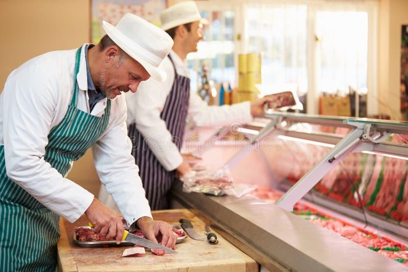 Due macellai che preparano carne in negozio fotografie stock