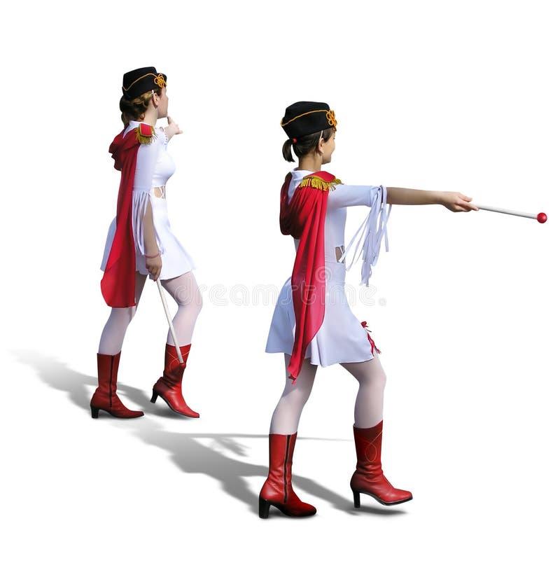 Due Majorettes con i vestiti bianchi, i caricamenti del sistema rossi e le sciarpe fotografia stock
