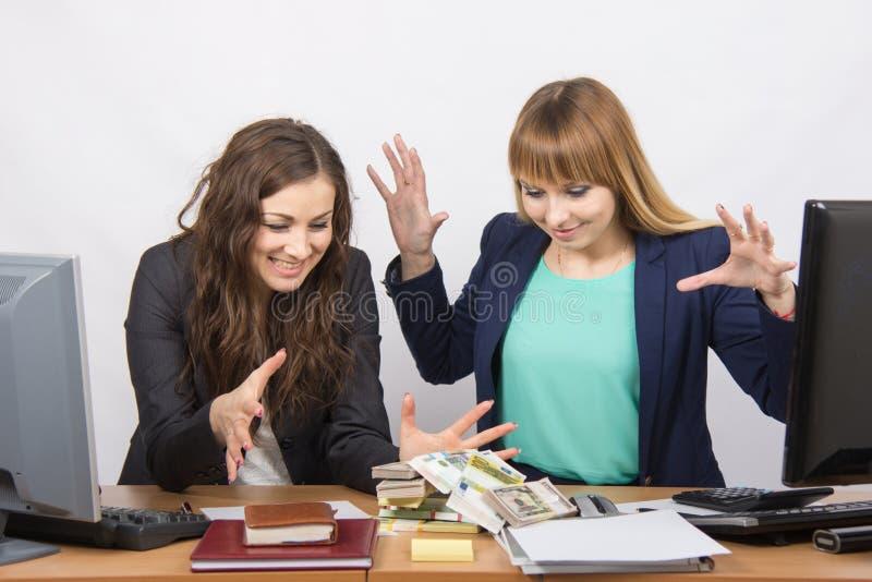 Due mani avide degli impiegati di ufficio per tirare un batuffolo di soldi fotografia stock