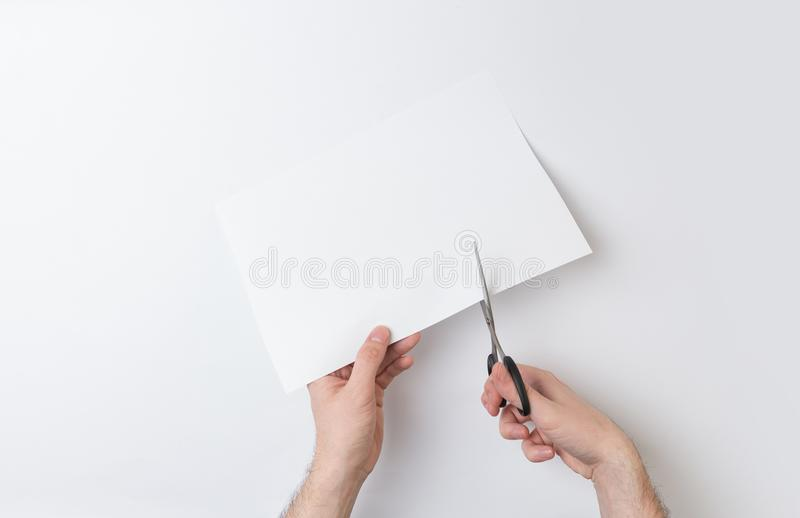 Due mani che tagliano carta fotografia stock