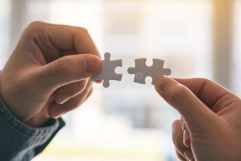 Due mani che tengono e che un un pezzo di puzzle bianco immagini stock libere da diritti