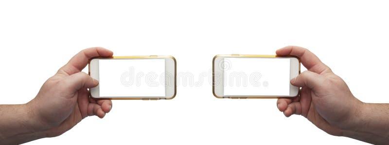 Due mani che tengono i telefoni cellulari su fondo bianco con gli schermi vuoti per il montaggio fotografie stock libere da diritti