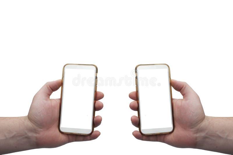 Due mani che tengono i telefoni cellulari su fondo bianco con gli schermi vuoti per il montaggio fotografia stock