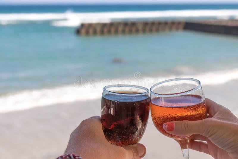 Due mani che tengono i vetri con vino sul fondo del mare Mani femminili e maschii con i vetri di vino fotografia stock