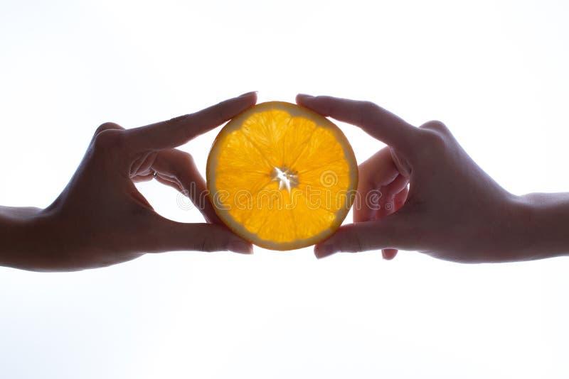 Due mani che tengono la fetta di arancia su fondo bianco immagini stock libere da diritti