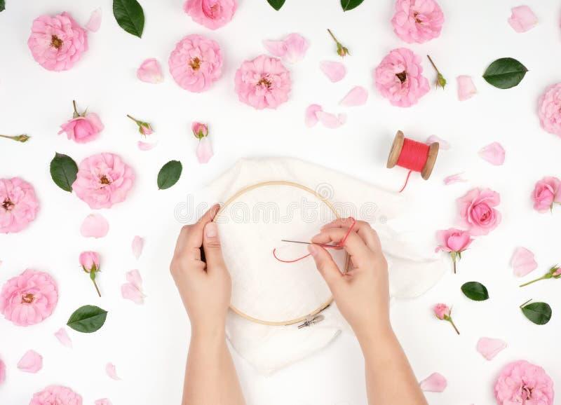 due mani femminili che tengono un cerchio di legno rotondo e un filo rosso fotografia stock