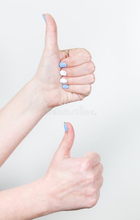 Due mani femminili nel gesto di somiglianza con il pollice su isolato immagini stock libere da diritti