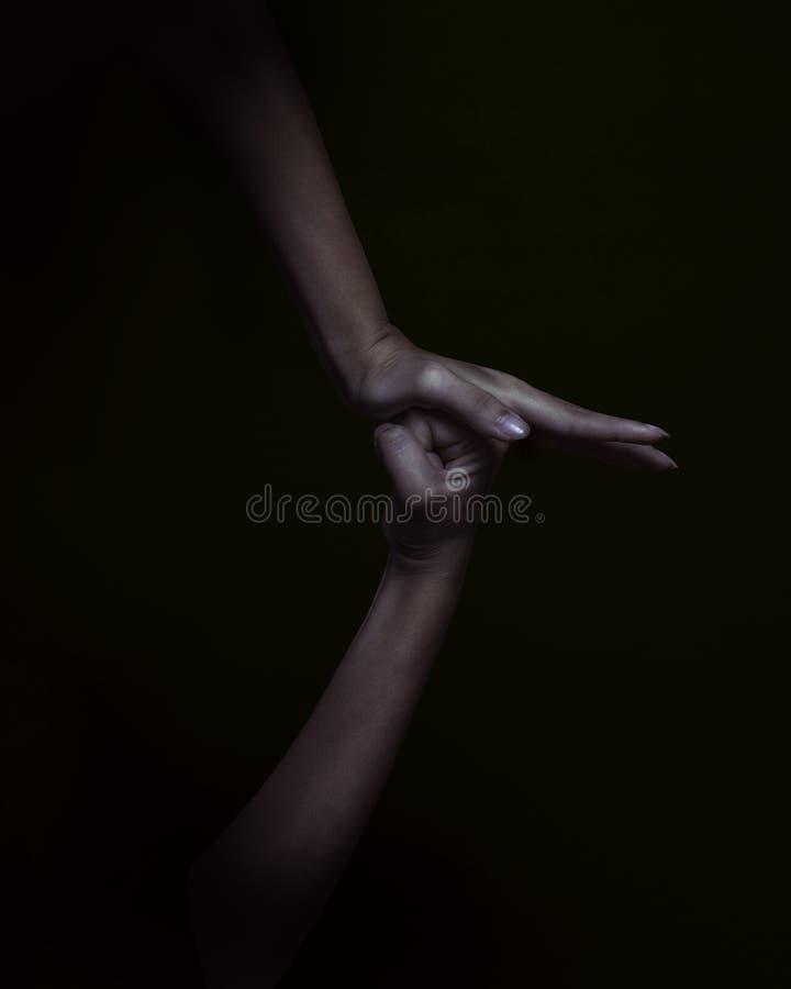 Due mani su fondo nero immagini stock