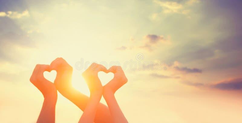 Due mani su sunsut immagine stock