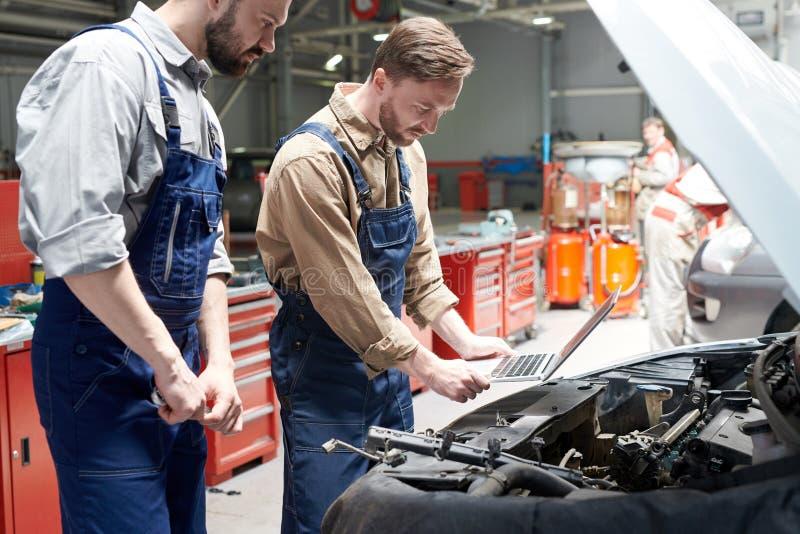 Due meccanici che ispezionano automobile immagini stock libere da diritti