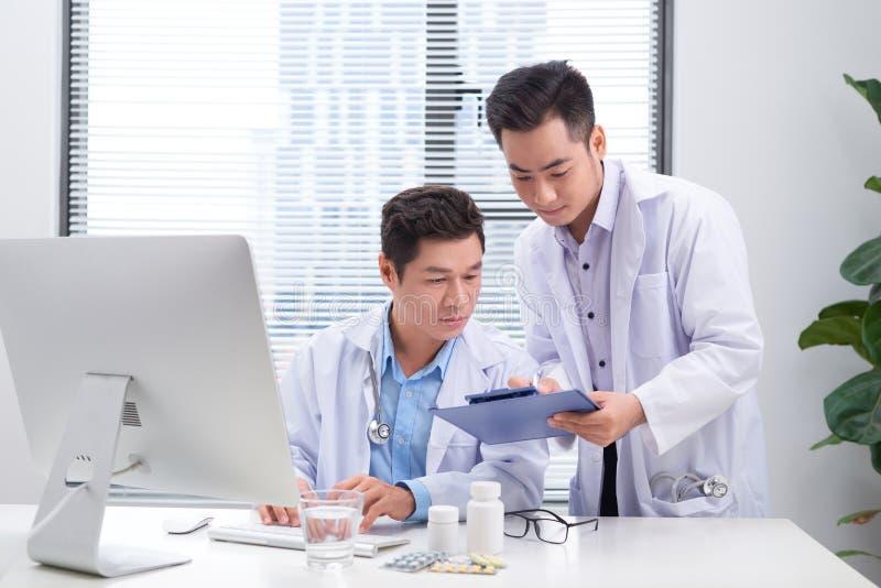 Due medici che discutono le cartelle sanitarie di un paziente fotografia stock libera da diritti