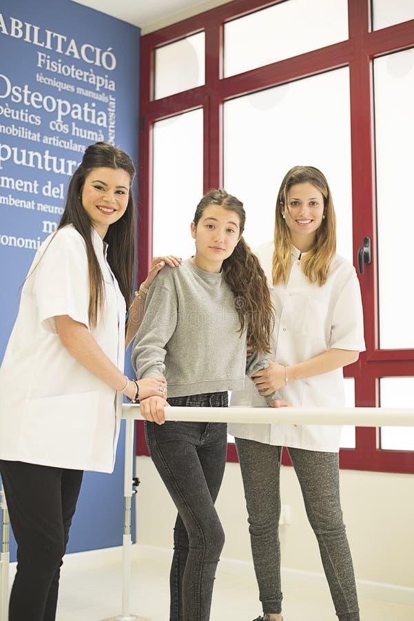 Due medici femminili che aiutano ragazza a camminare immagini stock