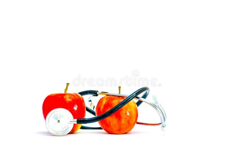Due mele mature rosse con uno stetoscopio su un fondo bianco immagini stock libere da diritti