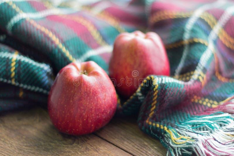 Due mele rosse si trovano su una tavola di legno, su un plaid fotografia stock
