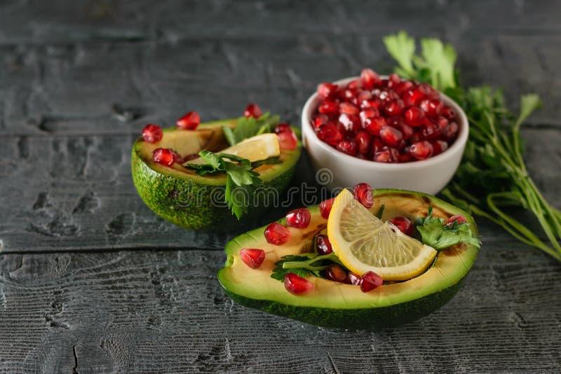 Due metà dell'avocado, delle foglie mature del melograno, del limone e del prezzemolo su una tavola di legno scura rustica fotografia stock