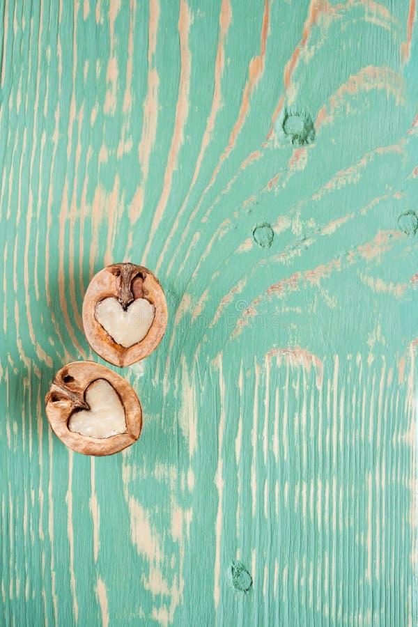 Due metà della noce come cuore stanno trovando sulla tavola di legno verde chiaro con le bande e le macchie deformate immagini stock