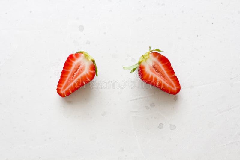 due met? delle fragole Belle fragole rosse tagliate su un fondo concreto bianco leggero Disposizione piana, vista superiore, spaz fotografia stock
