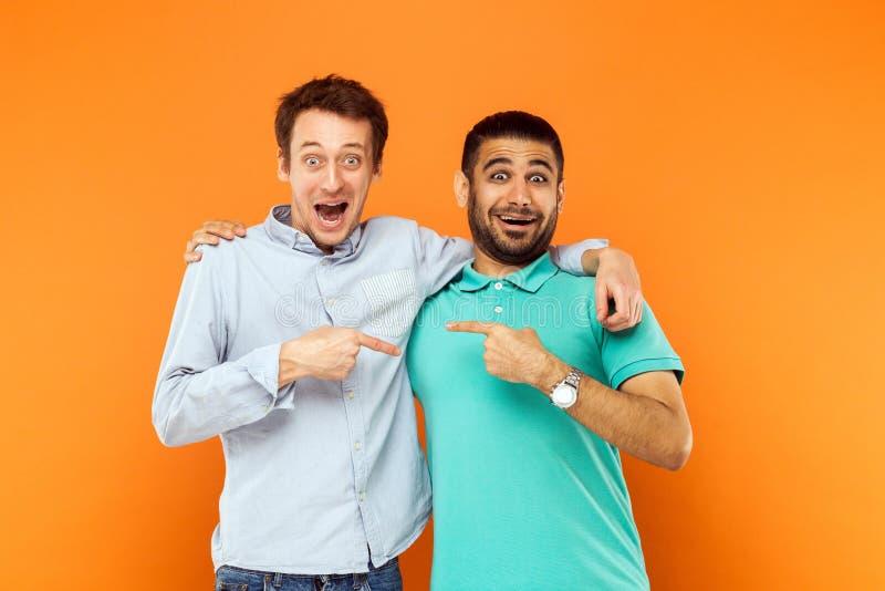 Due migliori amici che abbracciano, indicando dito e guardare immagini stock libere da diritti