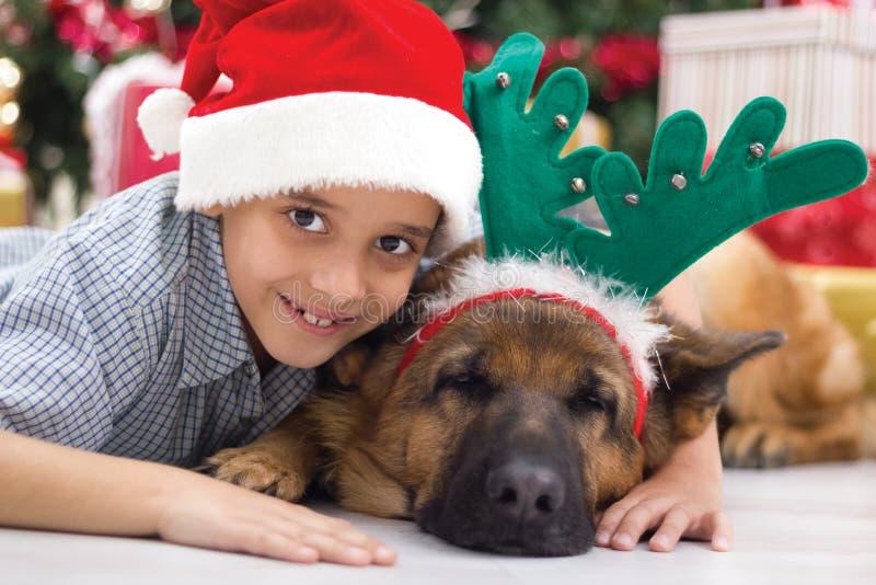 Due migliori amici ragazzo e cane nella celebrazione di notte di Natale immagine stock