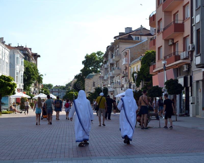 Due missionari della carità camminano lungo una via pedonale immagine stock libera da diritti