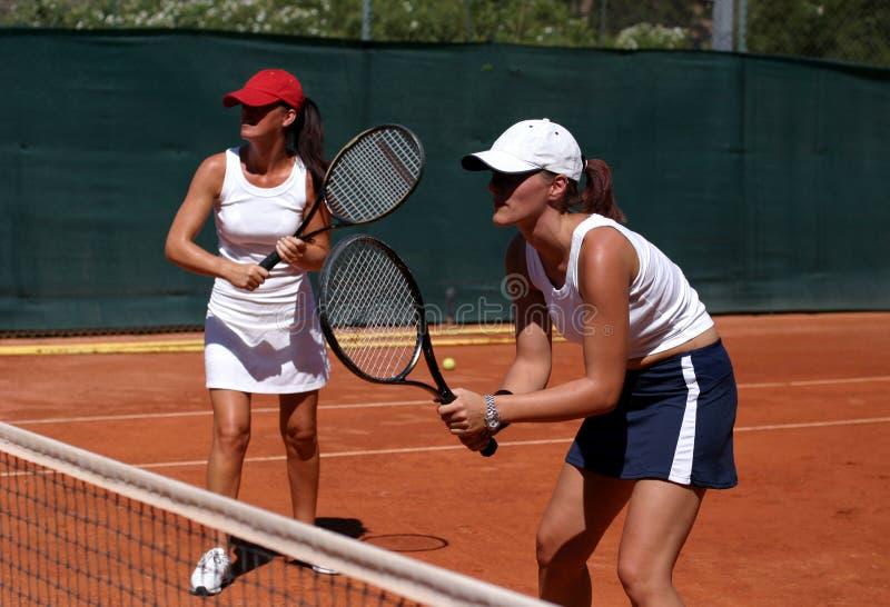Due misura, giovani, donne in buona salute che giocano i doppi al tennis al sole fotografia stock