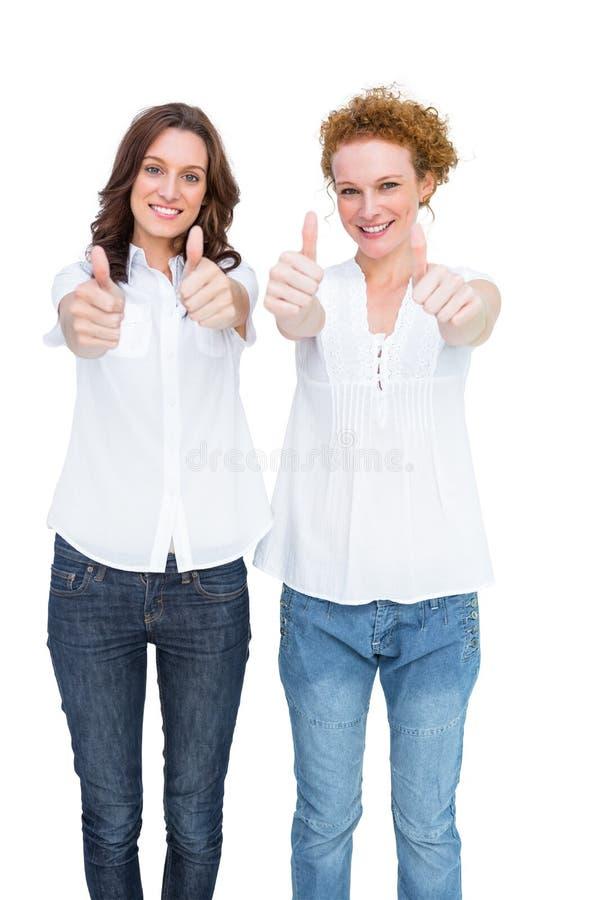 Due modelli casuali splendidi che posano con i pollici su fotografie stock