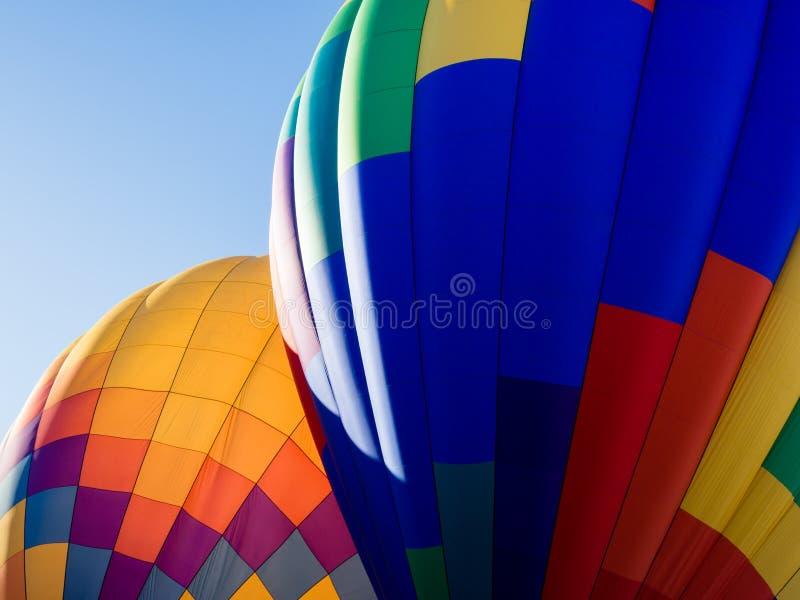 Due mongolfiere variopinte sulla terra fotografie stock libere da diritti