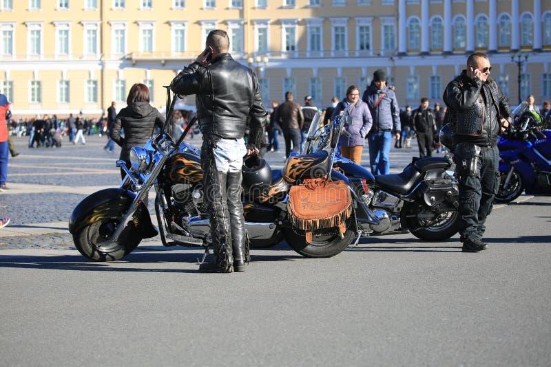 Due motociclisti che parlano sui telefoni, stanti alle loro motociclette fotografia stock libera da diritti