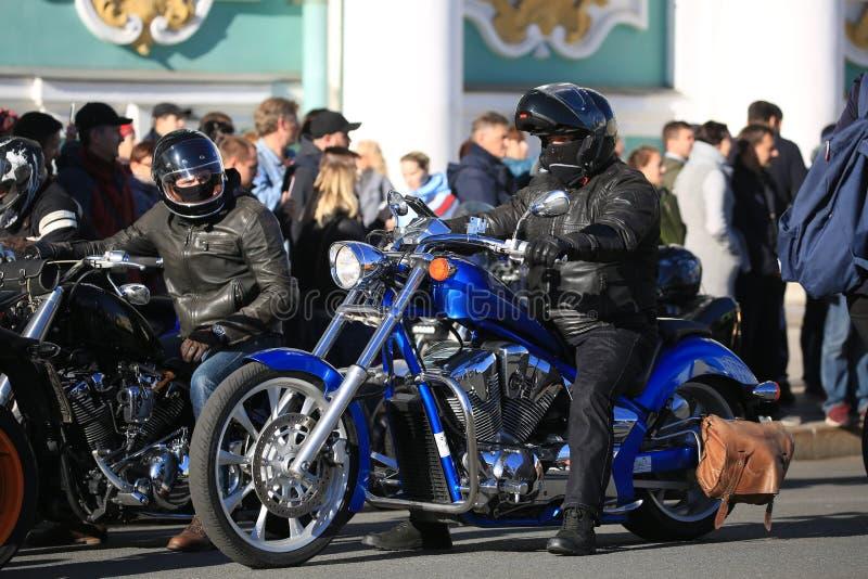 Due motociclisti sui loro motocicli sui precedenti degli spettatori fotografia stock libera da diritti