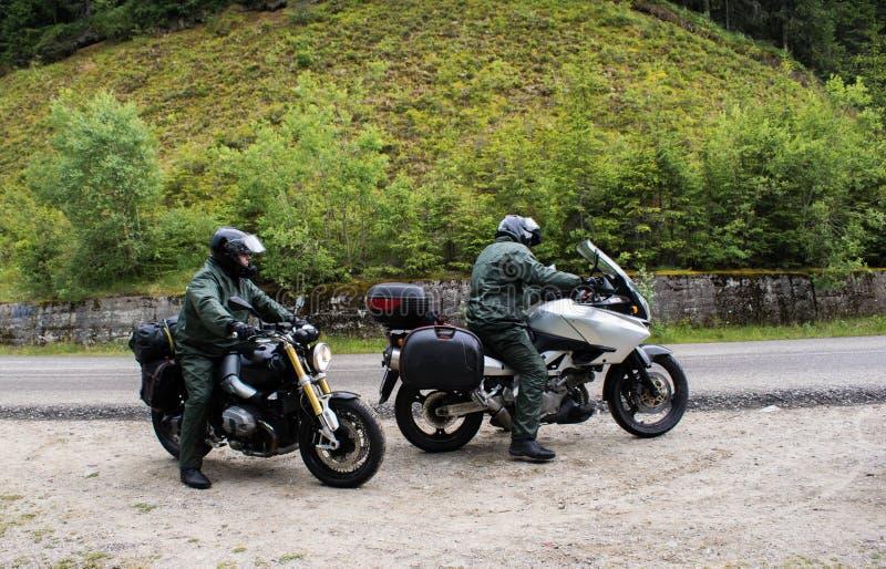 Due motociclisti sulle strade della montagna, hanno smesso di preparare per la pioggia che comincerà presto con il motociclo sull immagini stock libere da diritti