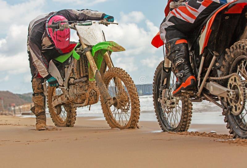 Due motociclisti in un vestito protettivo che si siede sulle motociclette di fronte ad a vicenda davanti al mare immagini stock libere da diritti